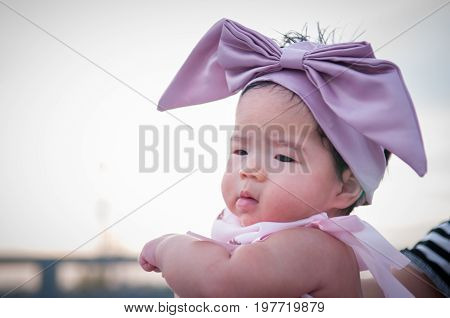 A shot of a cute baby girl with purple headband is holding by her mother. Focus at infant girl.