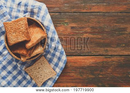 Breakfast background, white bread toasts in wicker breadbasket on checkered table napkin half covering wooden table, top view, copy space