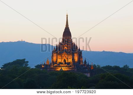 A view of the top of the ancient Buddhist temple off the Gawdaw Palin in the background of the twilight sky. Bagan, Burma