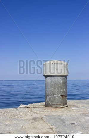 Concrete Bollard In The Harbor With The Sea Rope