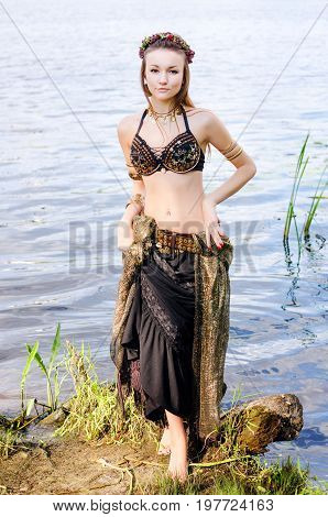 Young woman tribal american style dancer. Girl dancing and posing on the beach sand wearing belly dance costume. Ethnic dance. Belly dancing. Tribal dancing