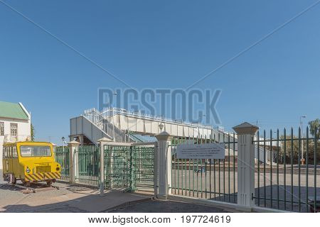 WINDHOEK NAMIBIA - JUNE 17 2017: A rail track inspection car on display with an entrance gate and pedestrian bridge at the railway station in Windhoek
