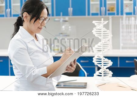 During the research. Serious nice smart researcher holding her notes and writing down her observations while conducting a genetic research