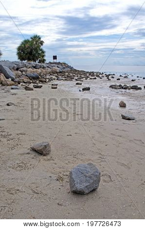 Low tide beach with stones and rocks, on an overcast and cloudy day. Crystal Beach, Florida, USA.