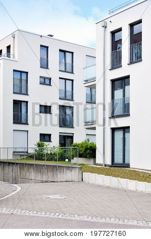 Leonberg, Baden-Wurttemberg, Germany - April 23, 2017: Modern white residential elite low-rise houses with terraces and wide windows. Vertical view.