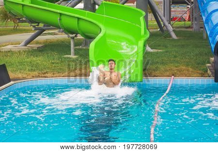 Man go down from water slide to swimming pool in aqua park.