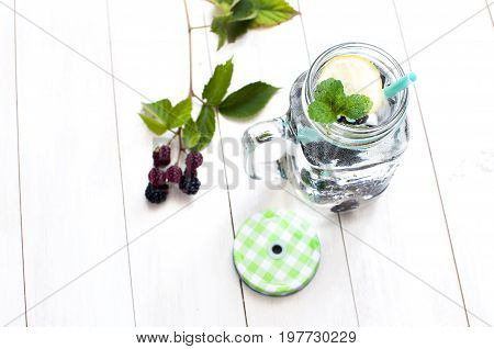 Summer drink with blackberries, lemon and mint in a glass jar on a white rustic wooden background with copy space top view.