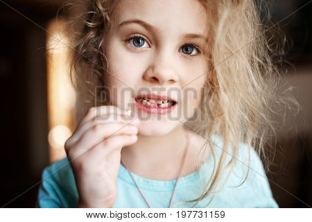 Smiling girl holding missing milk tooth, close up photo