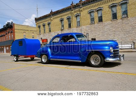 CASSELTON, NORTH DAKOTA, July 27, 2017: The annual Casselton Car Show which occurs the last Thursday of July features classic vehicles such as the 1948 Plymouth pulling a camper.