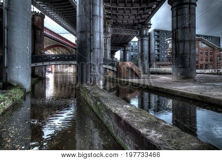 Dark and gloomy industrial atmosphere under the historical rail bridges in Manchester
