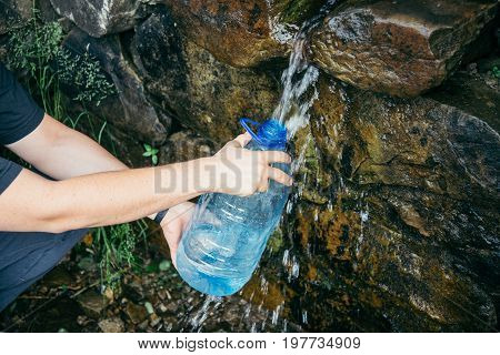 woman hands fill up the bottle from water source in mountains