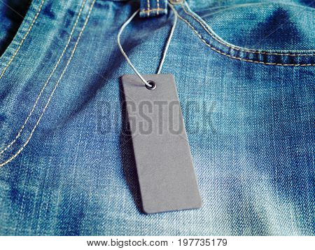 Blank gray label price tag on clothes jeans. Mock-up for price or brand presentation.