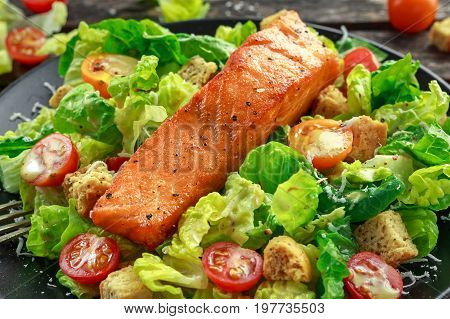 Caesar Salmon Salad with croutons, parmesan cheese, tomatoes, dressing and pepper in a black plate on wooden table