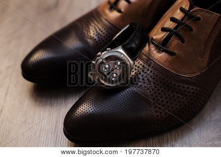 Man's style. Male shoes and watch in wooden table