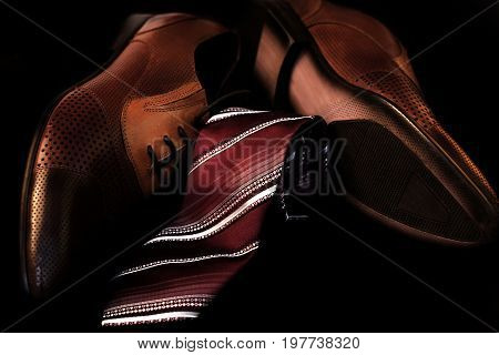 Man's style. Male shoes and tie over black