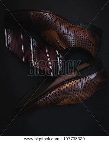 Man's style. Male shoes and tie over dark