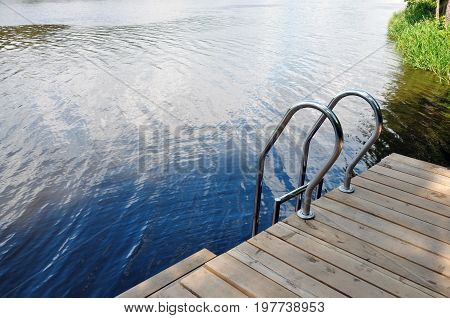 Wooden pier with metal railing on background of the river.