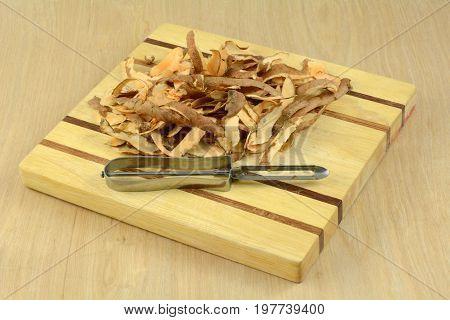 Sweet potato peelings and vegetable peeler on cutting board on wooden table