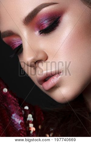Close up portrait of beautiful young model with professional makeup, perfect skin. Trendy colorful smoky eyes. Red and lilac smoky eyes