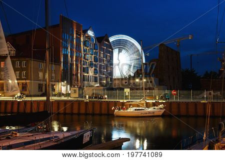 Gdansk Poland - July 22 2017: Yachts in the harbor against the background of illuminated apartments and ferris wheel at night