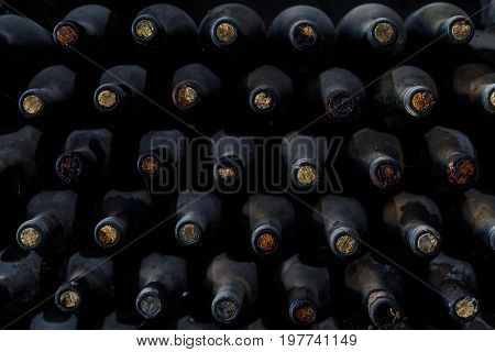 Stacked of old bottles in the cellar, wine in dark bottles covered with dust