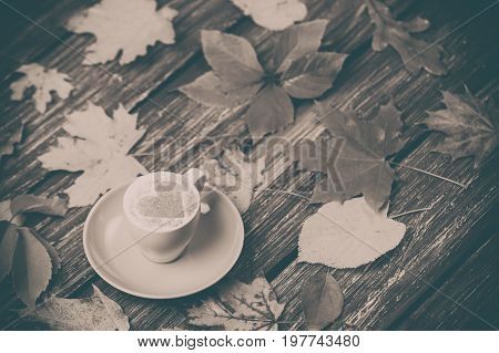 Autumn Maple Leaves And Coffee Cup On Wooden Table.