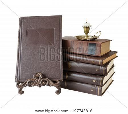 Old brown hardcover books and burning candle in antique copper candlestick isolated on white background with copy-space