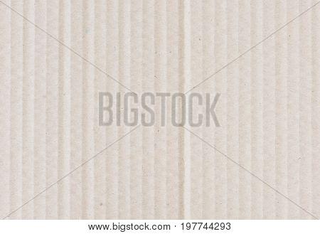 Beige background of kraft corrugated cardboard closeup