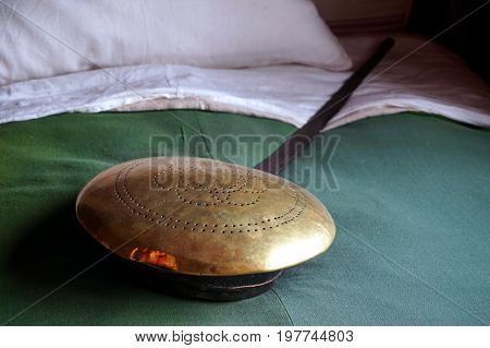 Traditional old brass bedpan laid on a bed with antique style bedclothes