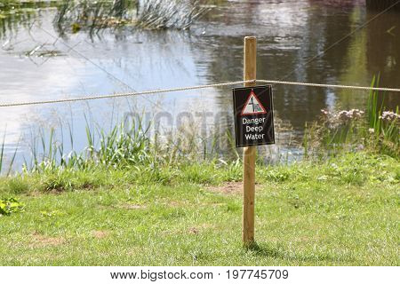 Notice On A Post In Front Of A Roped Off River Or Lake Saying