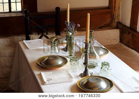 Pretty Tudor Dining Table In A Middle Class Medieval Home, Set With Candles, Glassware, Cotton Napki