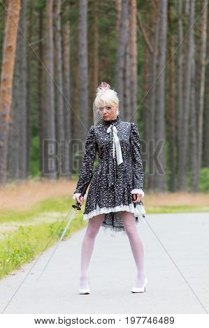 young blond woman holds the katana in hand