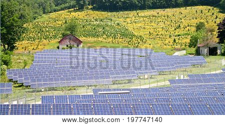 a solar farm with a red barn and a field of yellow flowers in the background