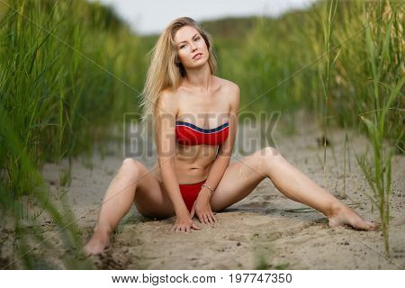 Woman with beautiful sports body on a beach
