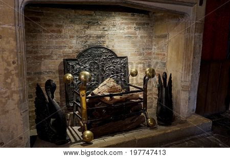 Traditional Medieval Fireplace And Hearth With Log Fire And Brass Surround