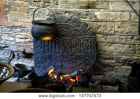 Traditional Old Antique Pots And Pans Over A Log Fire With Ornate Cracked Cast Iron Fire Back Agains