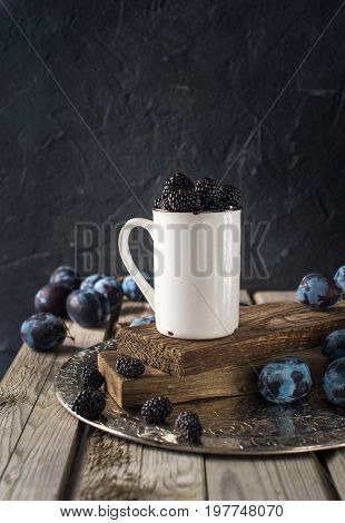 Ripe blackberries in a ceramic cup over wooden background close up. Rustic style