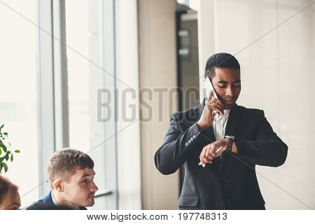 handsome african american businessman talking phone and looking watch