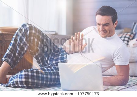 Say hello. Happy man looking at his laptop while having video conversation, keeping smile on his face
