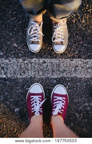 Sneakers On The Road. Road. Red Sneakers On Asphalt, Top View.  Teenager's L Shoes Stands On Asphalt