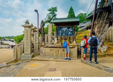 Nara, Japan - July 26, 2017: Unidentified people walking at the principal gate with old traditional architecture and street in Nigatsu-do, Todai-ji temple, Nara, Japan.