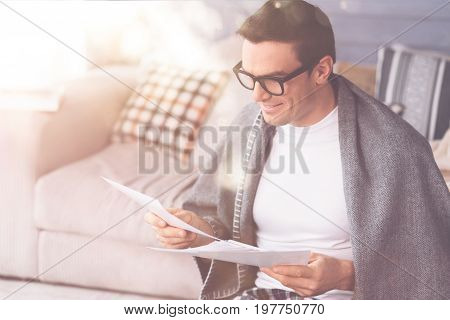 Just read it. Positive delighted man wearing glasses covering himself with plaid looking at papers that being in his hands