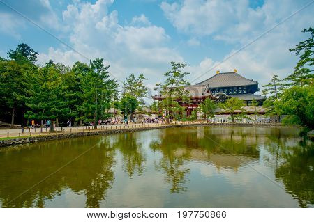 Nara, Japan - July 26, 2017: Unidentified people walking to Todai-ji temple with an Eastern Great Temple behind, and a beautiful artificial lake with tree reflections. This temple is a Buddhist temple located in the city of Nara, Japan.