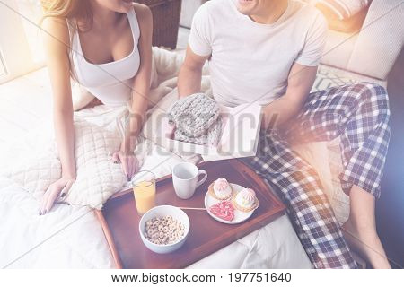 From me to you. Young sexy woman putting her hands on the pillow turning her head to boyfriend while sitting on the rug