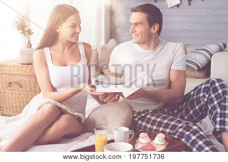 Like it very much. Positive delighted man turning his head to girlfriend giving box with present to her while feeling happiness