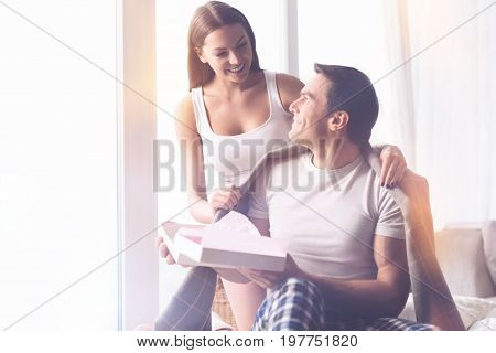 Happy with you. Sporty male person sitting in semi position looking at his girlfriend, giving box with present to her