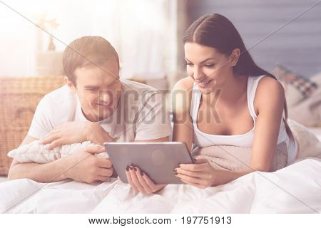 Lets choose. Two positive people lying on the blanket keeping smile on their faces while looking at their device
