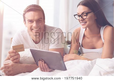 We can buy everything. Smiling female wearing stylish glasses holding tablet in right hand while lying on the blanket