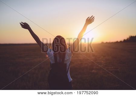 Portrait Of Happy And Enjoying Young Woman On A Meadow On A Sunset. Cheerful Girl On Sunset. Lifesty