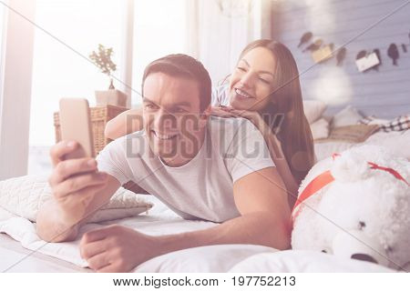 Say cheese. Handsome man holding telephone in right hand while posing on camera